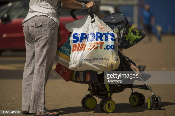 A Sports Direct International Plc carrier bag hangs on a pushchair in Crayford UK on Monday July 29 2019 Sports Direct plunged after the UK retailer...