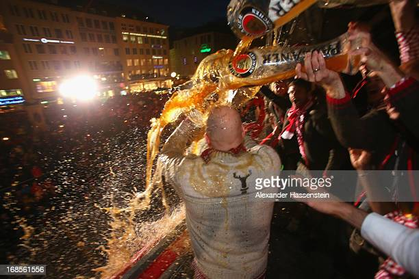 Sports director Matthias Sammer of Bayern Muenchen is poured with beer while celebrating the German championship title on the town hall balcony at...