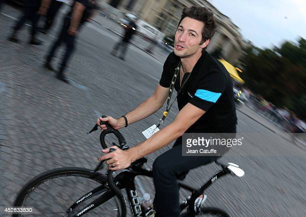 Sports director of Team Sky Nicolas Portal rides a bike during the lap of honor after the twenty one and last stage of the 2014 Tour de France a 134...