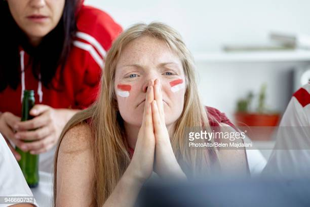 Sports enthusiasts anxiously watching match on TV