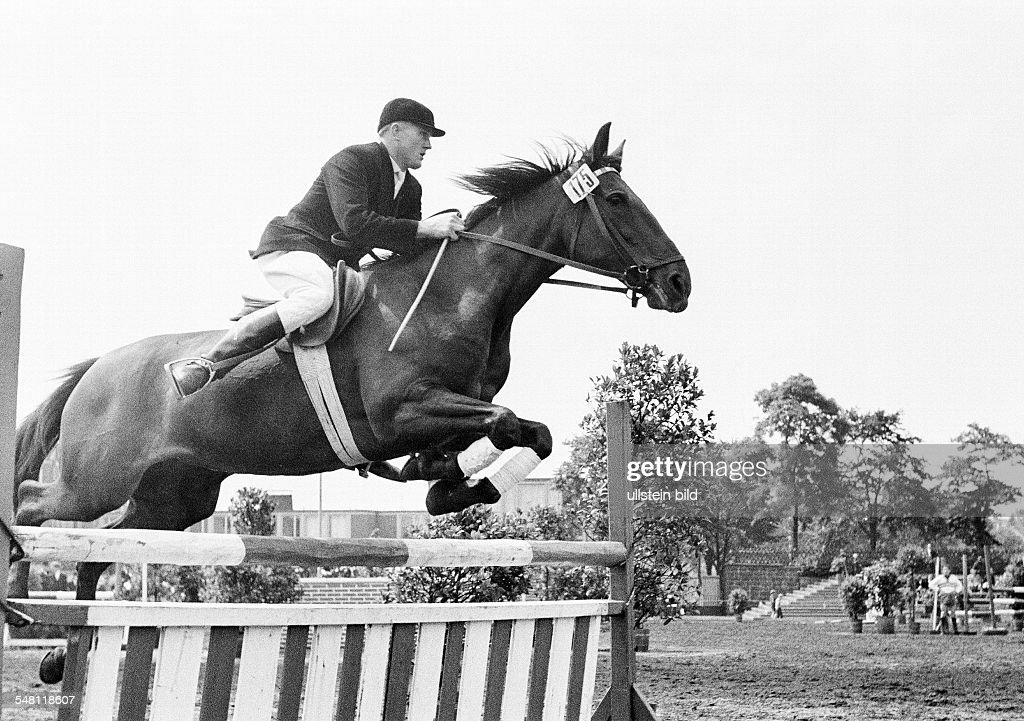 sports, equestrianism, horse show 1965 in Bottrop, show jumping, horse and horseman jump over a barrier, aged 30 to 40 years, D-Bottrop, Ruhr area, North Rhine-Westphalia - 31.07.1965 : News Photo
