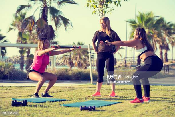 Sports event for young women. Squat exercise.