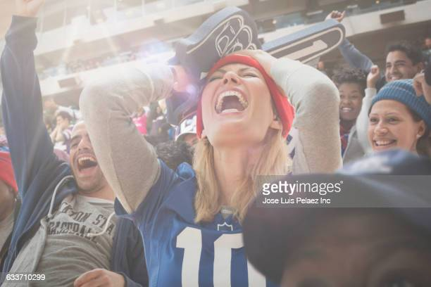 sports fan cheering in stadium - fan enthusiast stock photos and pictures