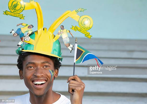 Sports fan wearing makarapa hat and waving small South African flag. Cape Town, Western Cape Provinc