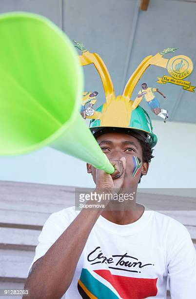 Sports fan with South African flag painted on his cheek blowing a vuvuzela. Cape Town, Western Cape
