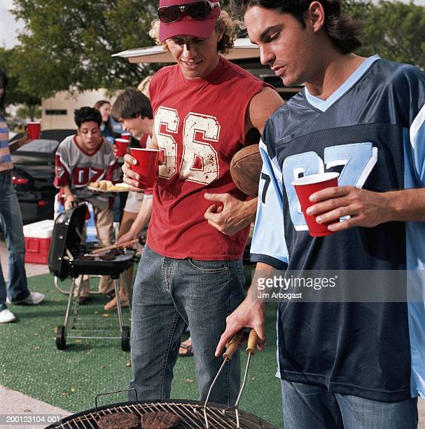 Sports fans at tailgate party (focus on two men using barbecue grill)