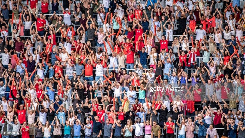 Sports fans in red jerseys cheering on stadium bleachers : Stock Photo