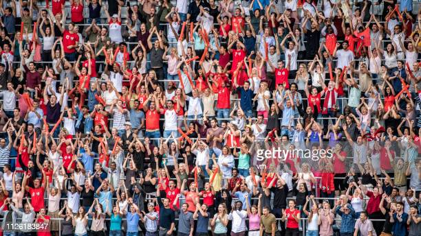 sports fans in red jerseys cheering on stadium bleachers - supporter stock pictures, royalty-free photos & images