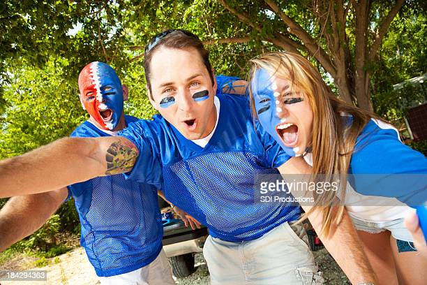 sports fans screaming at a tailgate party - face paint stock pictures, royalty-free photos & images