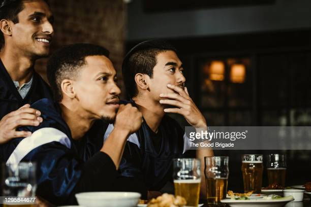 sports fans sitting at bar in pub drinking beer - fan enthusiast stock pictures, royalty-free photos & images