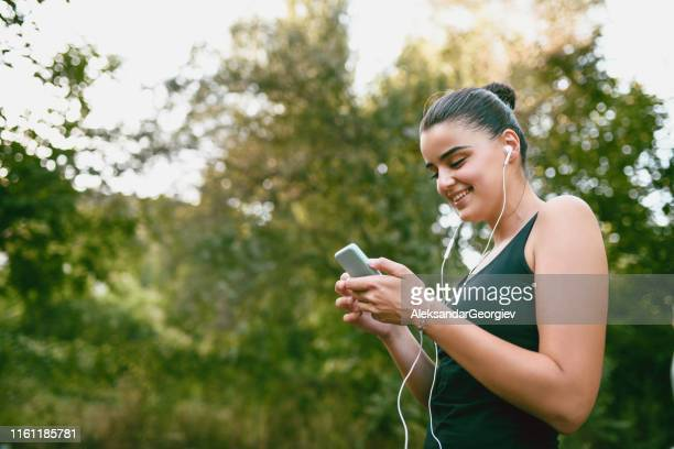 sports female texting her friends to join her training - colors soundtrack stock pictures, royalty-free photos & images