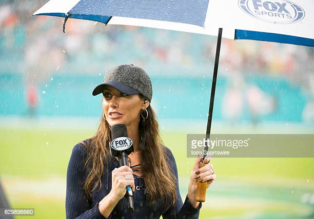 Sports field reporter Holly Sonders holds a microphone and umbrella in the rain on the field after the NFL football game between the Arizona...