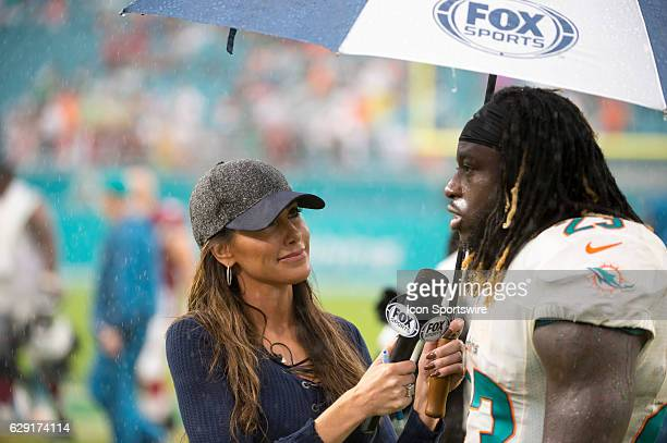Sports field reporter Holly Sonders interviews Miami Dolphins Running Back Jay Ajayi in the rain on the field after the NFL football game between the...