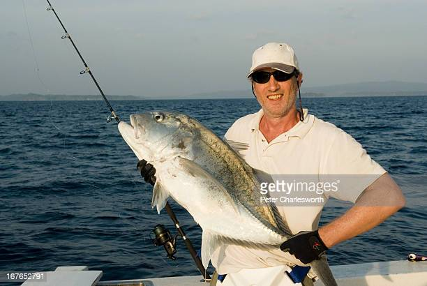A sports fisherman displays his catch a Giant Trevalli or Caranx ignobilis while on a biggame fishing trip to the Andaman Islands MODEL RELEASED