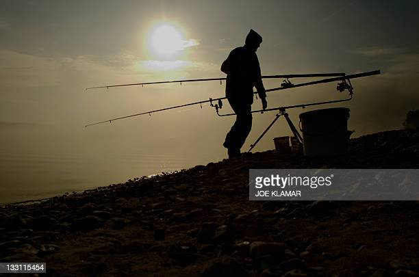 A sports fisherman prepares his gear early morning while enjoying one of the last days of Indian summer at Liptovska Mara dam on October 19 2011...