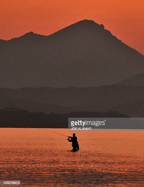 A sports fishermen tries his luck on a flooded old road after sunset at Liptovska Mara dam near the city of Liptovsky Mikulas on June 21 2010...