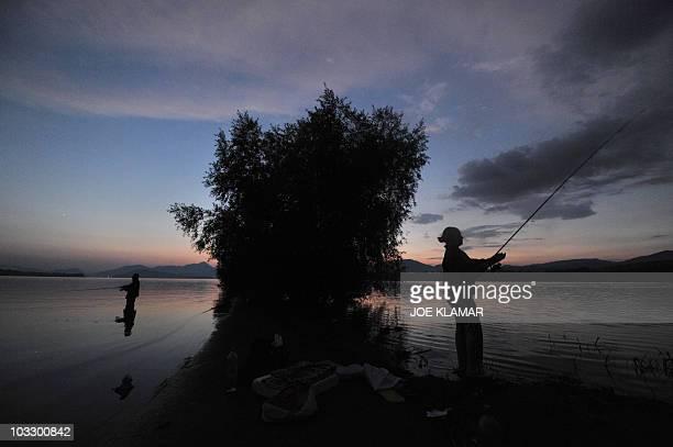 Sports fishermen try their luck on a flooded old road after sunset at Liptovska Mara dam near the city of Liptovsky Mikulas on June 21 2010 Liptovska...