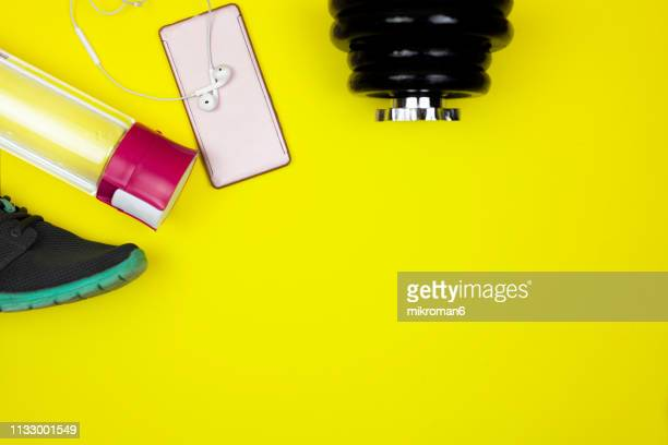 sports gear ready for the gym on yellow background - marathon stock pictures, royalty-free photos & images