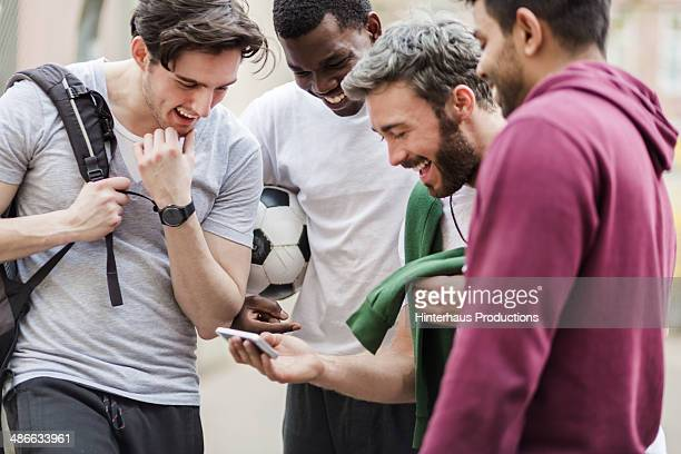 sports guys with smart phone having fun - calcio sport foto e immagini stock