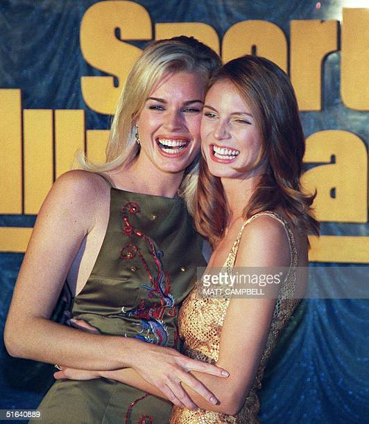 Sports Illustrated swimsuit edition models Heidi Klum who appears on the 1998 cover and Rebecca Romijn pose for the cameras during the launch of the...