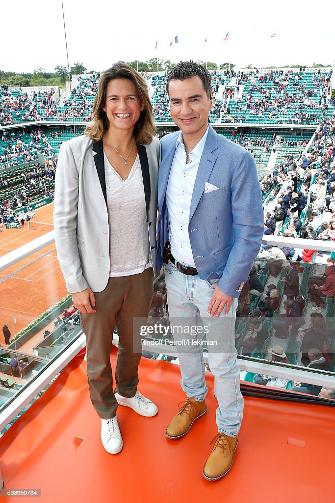 Sports journalist Laurent Luyat (R) poses with his Co-Presenter Amelie Mauresmo (L) at France Television french chanel studio during the 2016 French Tennis Open - Day Three at Roland Garros on May 24, 2016 in Paris, France.