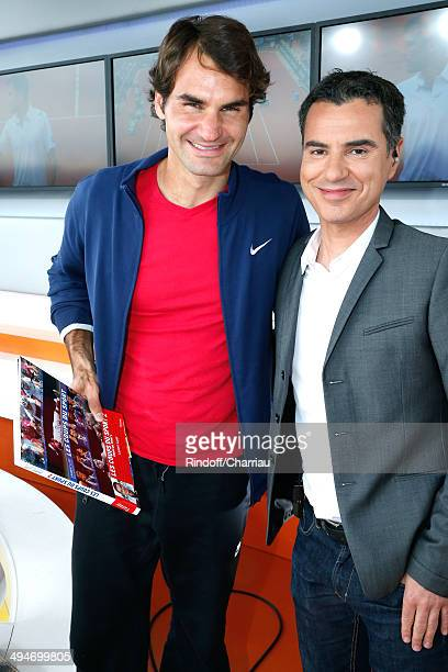 Sports journalist Laurent Luyat presents his book 'Les coups du sport' to tennis player Roger Federer at France Television french chanels studio...