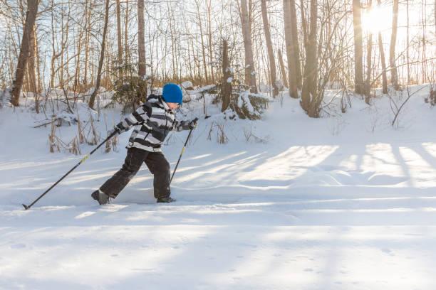 Sports little boy in snowy winter landscape on cross country ski against sun