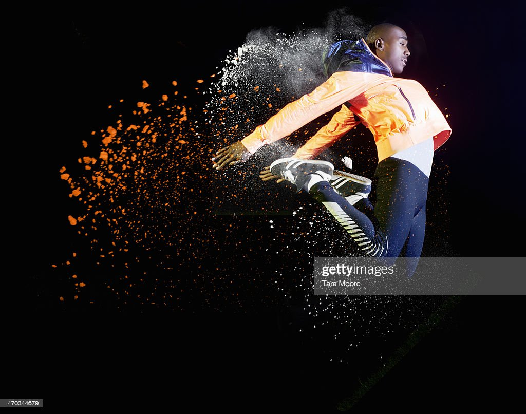 sports man jumping with coloured powder and smoke : Foto stock