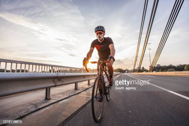 sports man riding bicycle - cycling helmet stock pictures, royalty-free photos & images