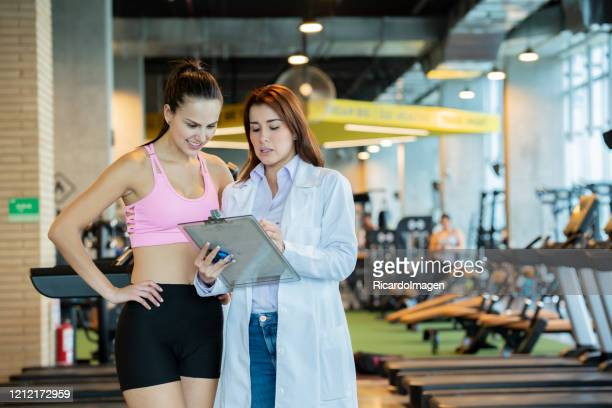 sports medicine shows instructions to a woman athlete - sports medicine stock pictures, royalty-free photos & images