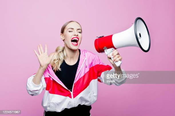 sports portrait of woman in tracksuit shouting into megaphone - candidate stock pictures, royalty-free photos & images