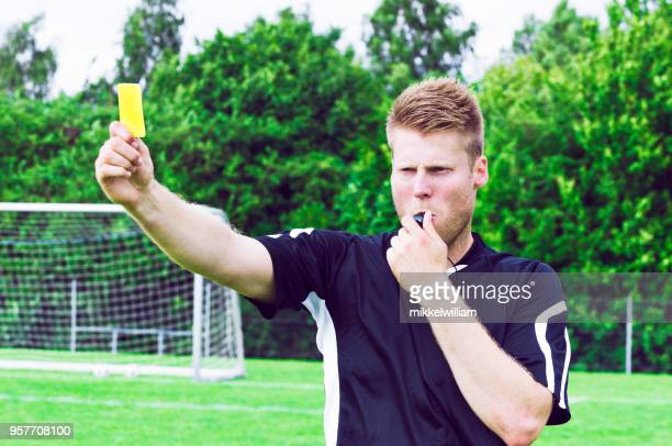 Sports referee blows whistle and shows yellow card