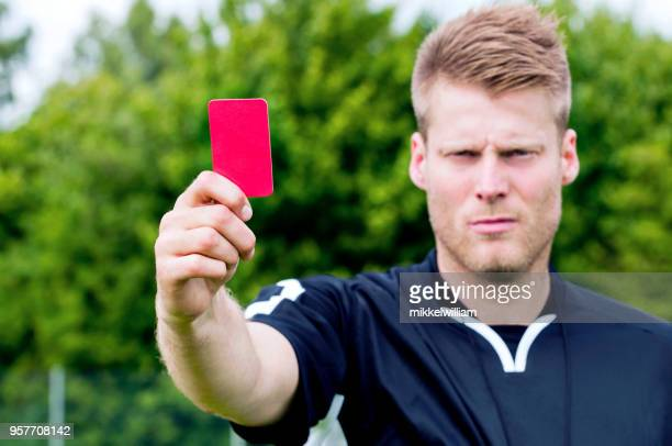 Sports referee shows red card after blowing his whistle