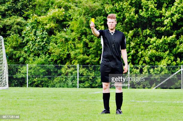 Sports referee shows yellow card after blowing whistle