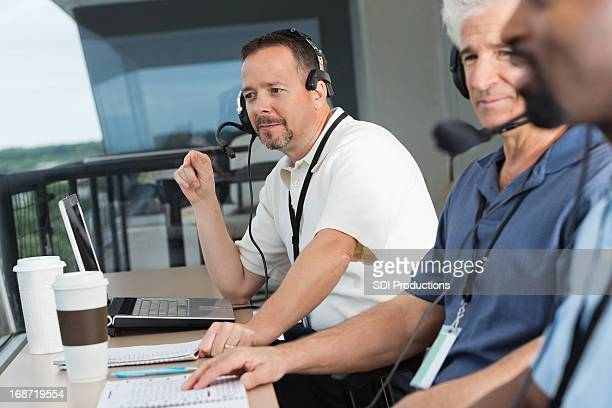 Sports reporters and commentators in stadium press box during game