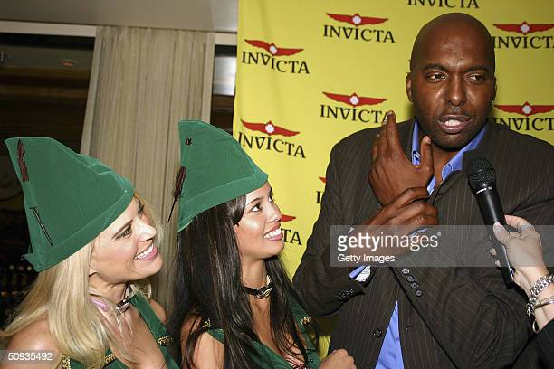 Sports show host John Salley describes the benefits of Invicta watches to an interviewer as models Amy Miller and Andrea Tiede listen on June 5 2004...