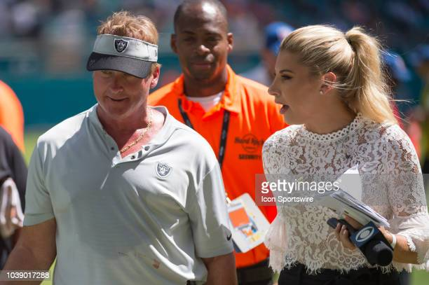 Sports sideline reporter Melanie Collins talks with Oakland Raiders Head Coach Jon Gruden as he walks off the field at the end of the second quarter...