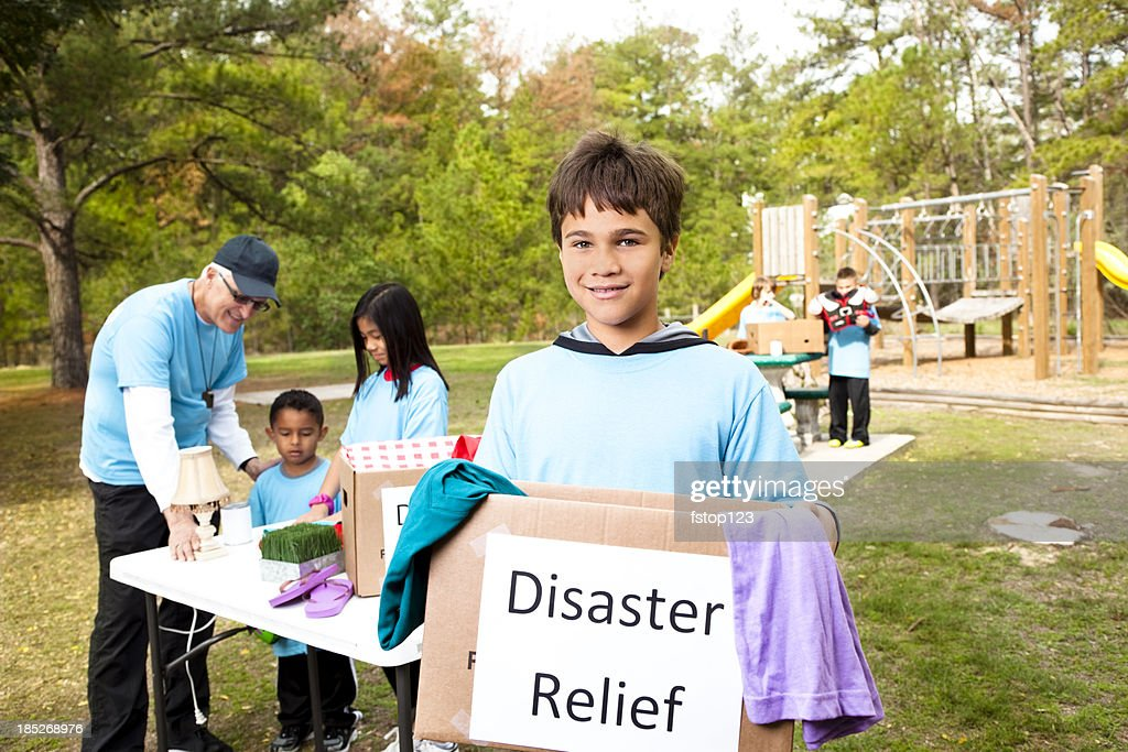 Sports team of children collecting for disaster victims : Stock Photo