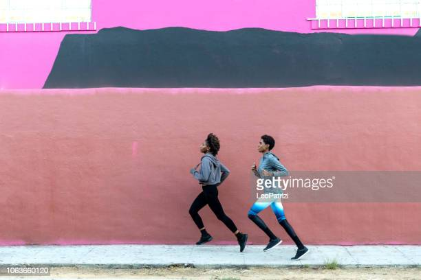 sports team running in the city. group of people getting fit - womens track stock photos and pictures