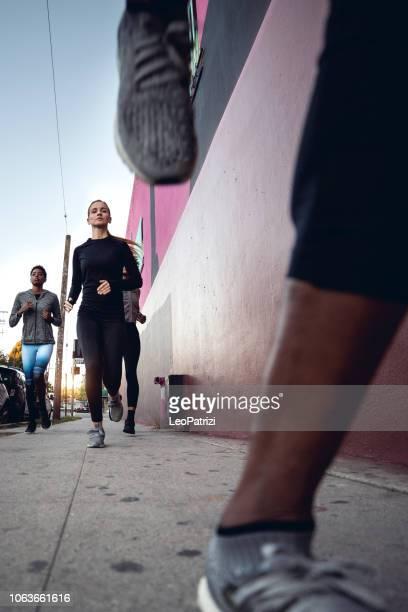 sport-team in der stadt laufen. gruppe von menschen, die immer passen - aufwärmen stock-fotos und bilder