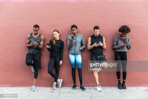 equipo de deportes en la ciudad. grupo de personas ponerse en forma - black pants fotografías e imágenes de stock