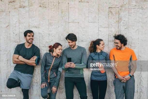 sports team using a smart phone - cinque persone foto e immagini stock