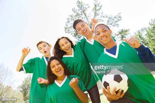Sports: Teenage friends soccer team with park background.