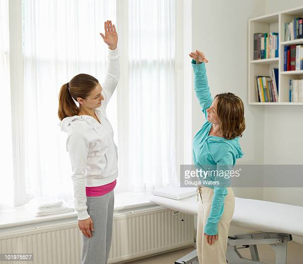 sports therapist demonstrating exercise. - newhealth stock pictures, royalty-free photos & images