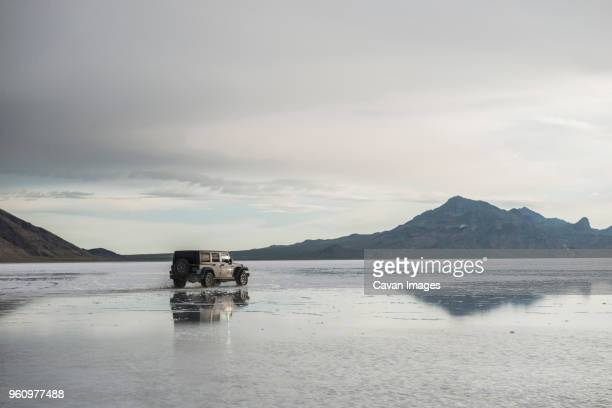 sports utility vehicle at bonneville salt flats against mountains and sky - bonneville salt flats stock pictures, royalty-free photos & images