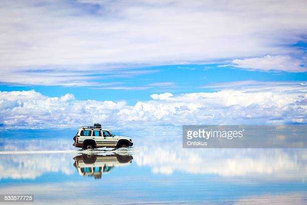 sports utility vehicle driving in the salar de uyuni - bolivia stockfoto's en -beelden