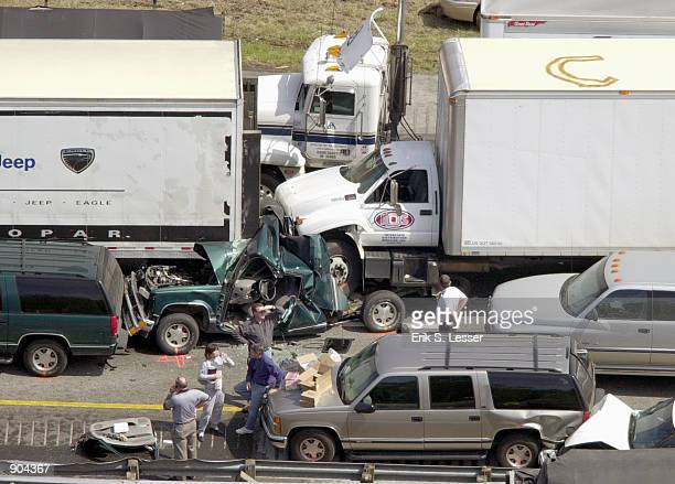 A sports utility vehicle is wedged between two trucks in a multiple car pile up along a foggy stretch of Interstate 75 March 14 2002 in Ringold in...