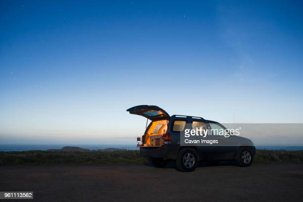sports utility vehicle parked on field against clear sky during dusk - car trunk stock pictures, royalty-free photos & images