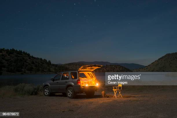 sports utility vehicle parked on shore by lake shastina against sky during night - land vehicle stock pictures, royalty-free photos & images