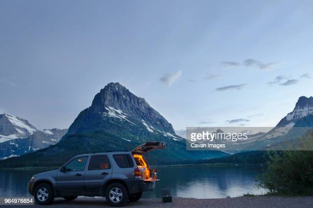 sports utility vehicle parked on shore of swiftcurrent lake against mt. grinnell - アウトドア ストックフォトと画像
